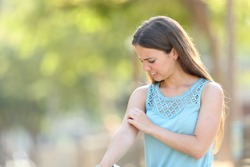 Woman scratching arm because it stings in a park with a green background