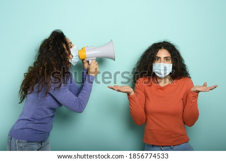 Woman screams with loudspeaker to a friend but it is difficult to understand with face mask. Cyan background Foto d'archivio ©