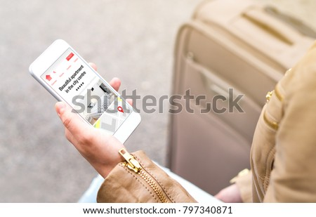 Woman search holiday apartments and rooms online with mobile phone. Vacation home rental website or application on smartphone screen. Traveler sitting next to suitcase, baggage or luggage.
