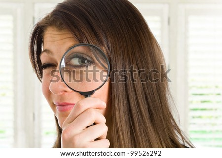 Woman searching for something using a magnifying glass