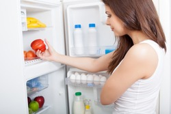 Woman searching in her fridge for fresh ingredients to prepare a meal