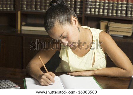 Woman seated at table in library writes in notebook. Horizontally framed photo.
