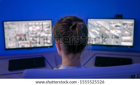 Woman security guard looking at modern cctv camera monitors in dark purple monitoring room with low light illumination. Surveillance, modern technology, control, safety of private property concept #1555525526