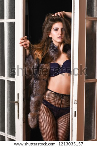 Woman seductive appearance. Confident in her magnetism. Seduction art concept. Woman seductive wear luxury fur and lingerie. Female lover enter bedroom doors. Fashion lady confident and seductive.