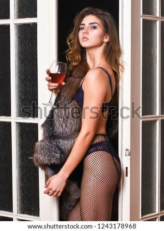 Woman seductive appearance. Woman seductive model wear luxury fur and elite lingerie. Confident in her magnetism. Seduction art concept. Girl enter bedroom doors. Fashion lady enjoy her seductiveness.