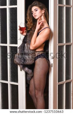 Woman seductive model wear luxury fur and elite lingerie. Seduction art concept. Girl enter bedroom doors. Fashion lady enjoy her seductiveness. Woman seductive appearance. Confident in her magnetism.