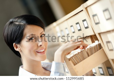 Woman seeks something in card catalog composed of set of wood boxes at the library. Study