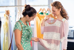 Woman selecting an apparel while shopping for clothes with her friend in a shop