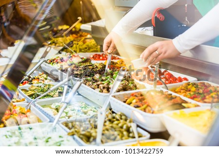 Woman selling Meze appetizers in delicatessen store