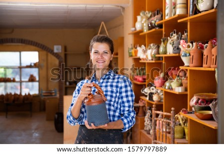 Woman sells handmade pottery in a store