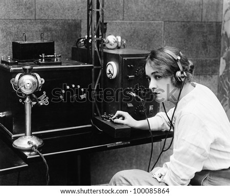 Woman sending Morse code using telegraph - stock photo