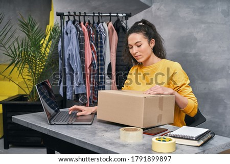 Woman sending parcel using her laptop. Working from home Photo stock ©