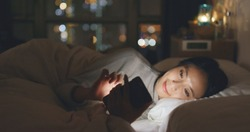 Woman sending sms on cellphone and lying on bed