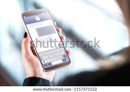 Woman sending text messages with mobile phone. Cellphone in hand with sms application on screen. Person using instant messaging software with smartphone. Texting and digital communication concept.