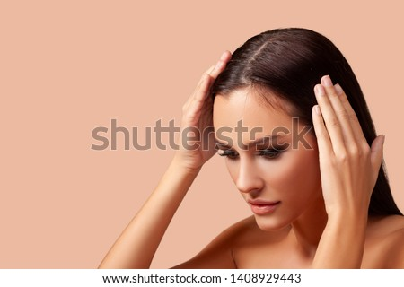Woman serious hair loss problem for health care Hair Care. Beautiful brunette girl posing in studio. isolated. beige background.- Image