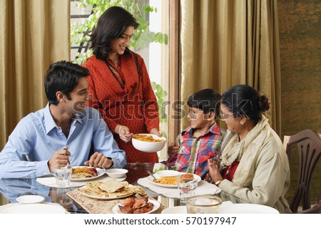 woman serves dinner to her family