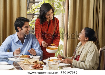 woman serves dinner to man and older woman (horizontal)