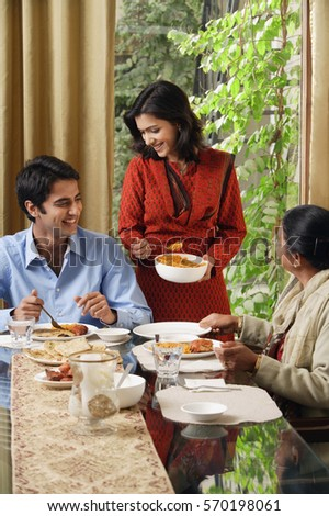 woman serves dinner to man and older woman (vertical)