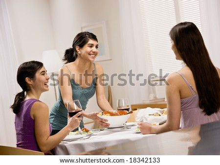 Woman serving spaghetti to friends gathered at dinner party