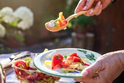 Woman serving vegetable salad by wooden spoon on plate. Enjoying healthy eating vegetarian food outdoors.