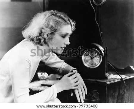 Woman setting watch to clock