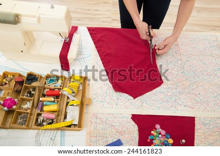 Woman sewing at home with sewing paper