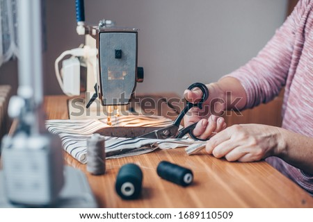 Photo of  Woman sewing medical masks on sewing machine during coronavirus pandemic, protection against covid-2019, homemade sewing
