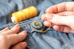 Woman Sewing on button. Thread needle Sewing Button Jeans. Close-up. Authentic Lifestyle. Hand made