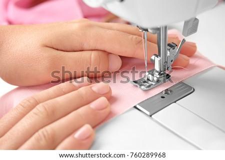 Woman sewing on machine, closeup #760289968