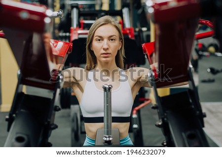 Woman shakes her legs over the bar. Fitness girl shakes leg muscles Stock photo ©