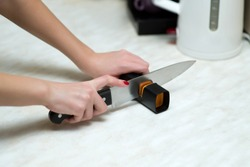 woman sharpening a knife with a special knife sharpener, close up