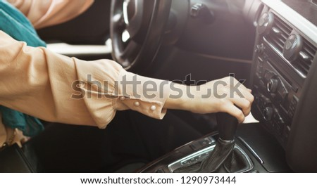 Woman shifting gear stick in car. Driving license test concept #1290973444