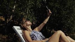 Woman shooting on handheld film gimbal stabilization for smartphone. Girl rest, relax, lie sunbed on pier in sunglasses, make selfie. Lady blogger broadcast video blogging vlogging. Take photo video.