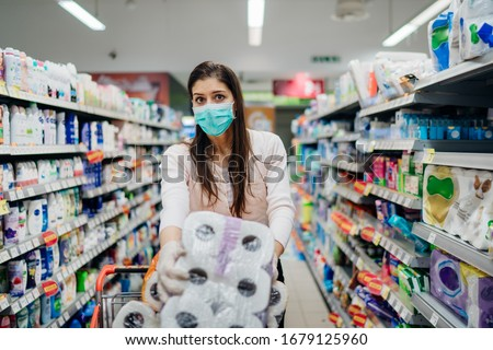 Woman shopper with mask and gloves panic buying and hoarding toilette paper in supply store.Preparing for pathogen virus pandemic quarantine.Prepper buying bulk cleaning supplies due to Covid-19.