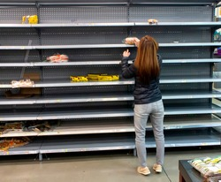 Woman shopping among empty shelves at a supermarket during coronavirus pandemic