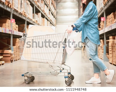 woman shopping and job concept from beauty asian girl in blue jean shopping in hardware store for support her construction job