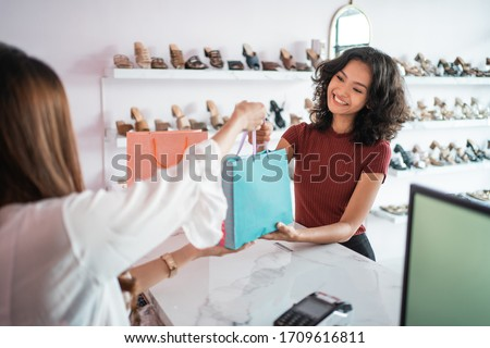 woman shopping at boutique store in the mall. shopping woman take paper bag Stock photo ©