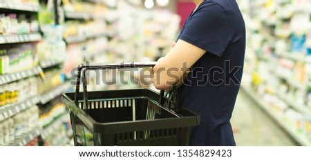 Woman Shopping at Grocery Market Pharmacy. Supermarket Shopper Doing Groceries. Female Holding Basket Trying to Decide which Products to Buy. Retail Healthcare Medicine, Vitamins, and Supplements.