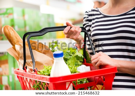 Woman shopping at store with shopping basket.