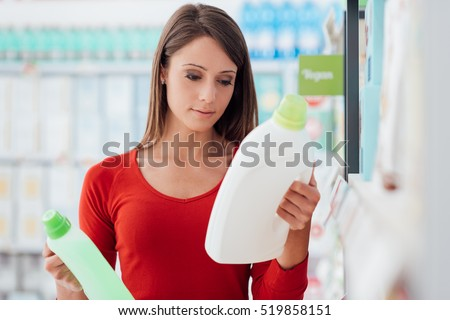 Woman shopping at the supermarket and comparing detergent products, she is reading labels Stock foto ©