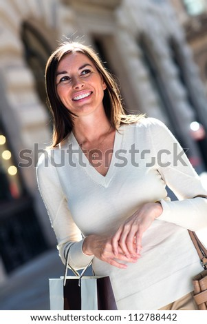 Woman shopping carrying bags and looking very happy