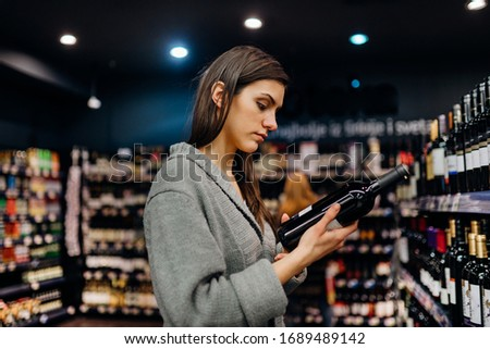 Woman shopping for expensive wine in supermarket alcohol store.Choosing and buying good cheap wine.Benefits of drinking wine.Resveratrol.Everyday binge drinking.Oenology.Mediterranean diet.Alcoholism Сток-фото ©