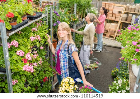 Woman shopping for flowers in garden center variation of plants