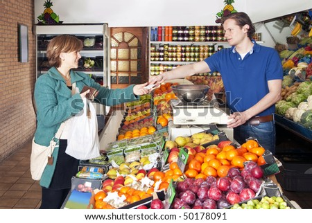 Woman shopping for fresh food and vegetables at a greengrocers' market