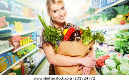 woman shopping for fruits and vegetables in produce department of a grocery store/supermarket