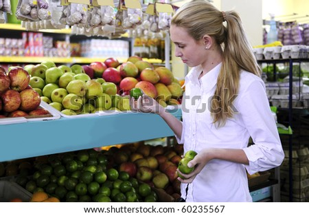 Woman shopping for fruits in the supermarket holding a lime