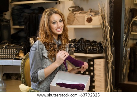 Woman shopping in a cloth shop with a box with shoes