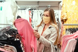 Woman shopping in fashion store wearing face mask looking at some clothes