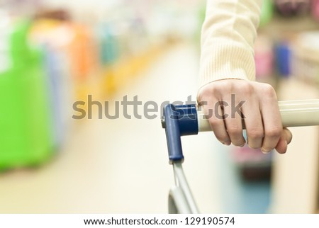 Woman shopping in super market and pushing cart hand closeup