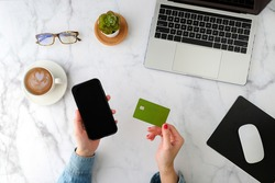 woman shopping online and pay on the mobile phone application with the green credit card. flat lay and modern style.